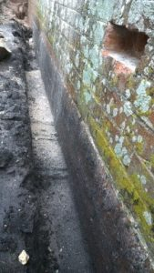 Stepped foundations and concrete plinth exposed during pentrating damp problem